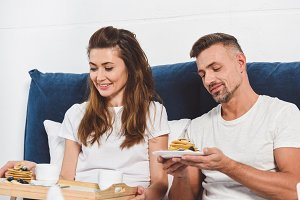 adult smiling couple eating pancakes