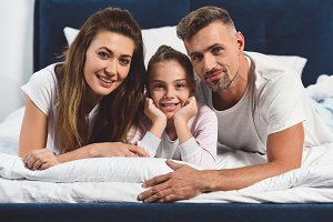 cheerful family laying in bed togeth