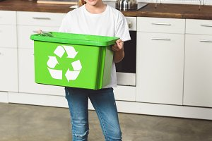 smiling child holding green recycle