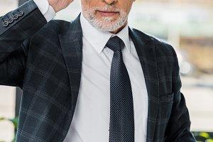 confident mature businessman adjusti
