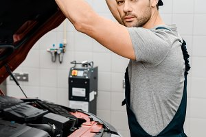 auto mechanic looking at camera whil