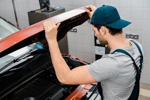 side view of auto mechanic examining