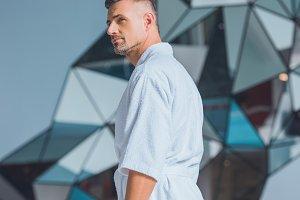 Handsome man standing in white bathr