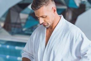 Handsome man untying bathrobe near p