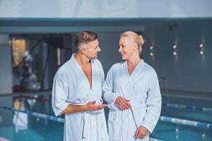 Happy couple standing in bathrobes i