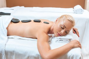 Woman lying on massage table with ho