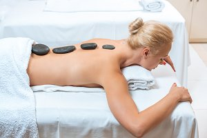 Beautiful woman lying with hot stone