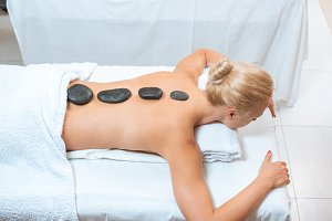 Woman with hot stones on back in spa