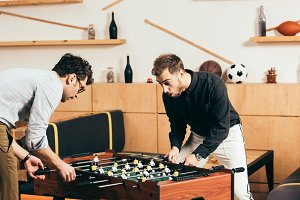 young friends playing table soccer i