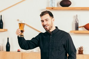 happy man with glass of beer looking