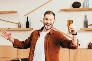 happy man with glass of beer in cafe