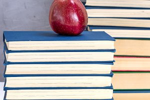 ripe red apple on a stack of books