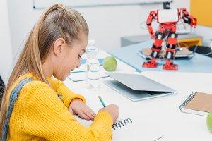schoolgirl sitting at desk with robo