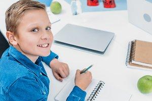 smiling boy writing in notebook, smi
