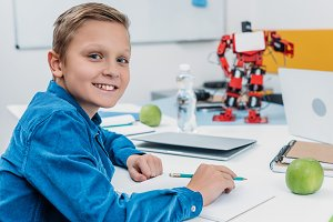 schoolboy sitting at desk with robot