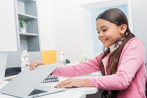 smiling schoolgirl sitting at desk a