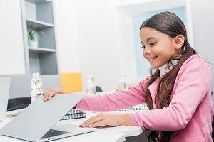 smiling schoolgirl sitting at desk a