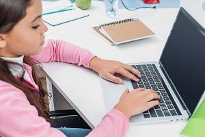 schoolgirl sitting at desk and using