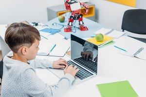 schoolboy typing on laptop keyboard