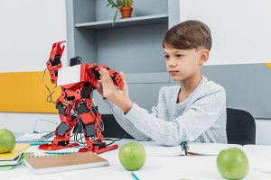 attentive boy working with a robot a