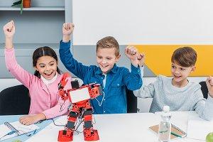 happy schoolchildren raising hands a