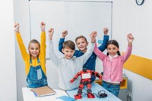 happy schoolchildren raising hands,