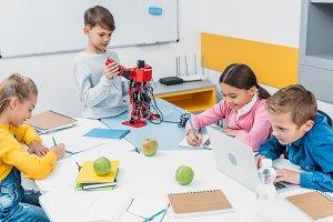 schoolchildren writing, using laptop
