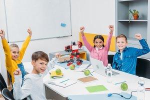 schoolchildren joying and raising ha