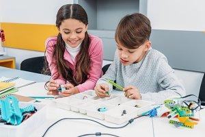 schoolchildren working on robot at S