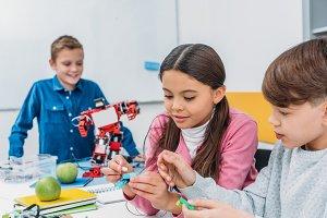 happy classmates making a robot duri