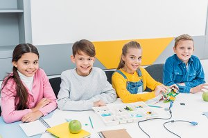 happy classmates at desk looking at
