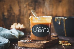 Caramel sauce in jar on wooden table