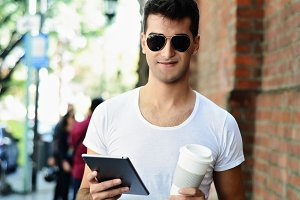 Man with tablet and drinking coffee