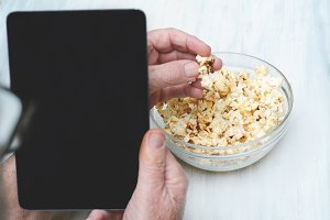 Popcorn in bowl and tablet with blac
