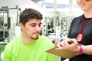 man with personal trainer in gym