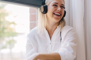 Laughing woman listening to music on