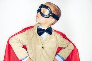 Cute little superhero boy looking up