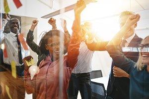 Ecstatic businesspeople cheering tog