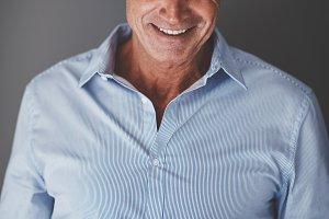 Smiling mature businessman reading t