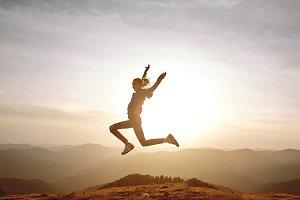 woman jumping on mountain on sunset