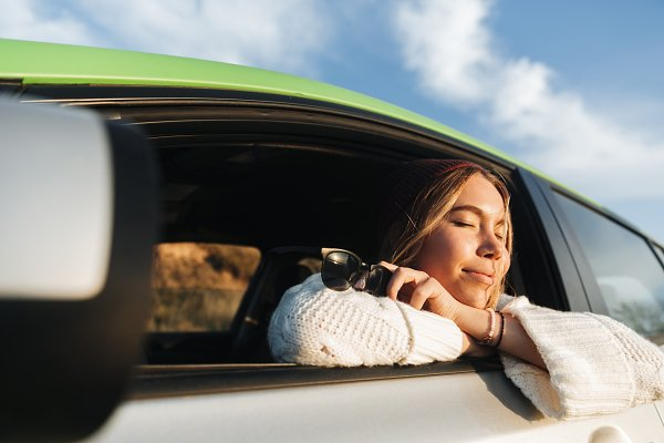 People Stock Photos: Royalty-free images - Smiling young girl driving a car dur