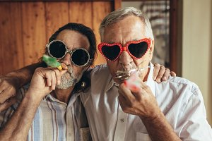Two old friends with party blowers