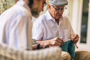 Two old men sitting knitting