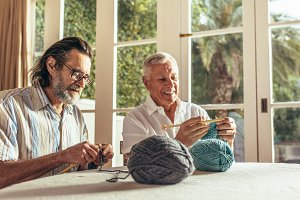 Senior people learning knitting