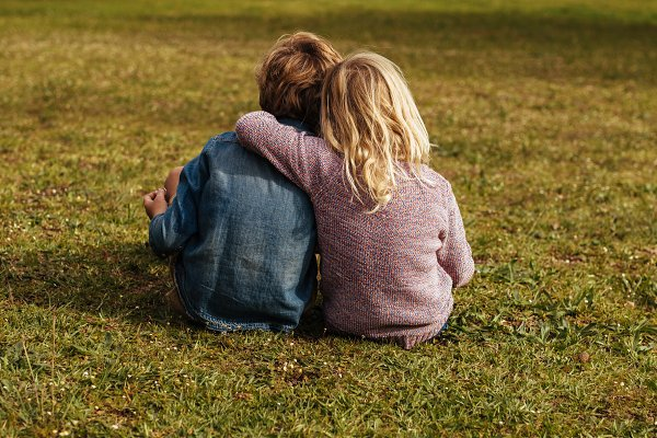 People Images: Jacob Lund - Siblings sitting on the grassy lawn