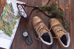 Old boots, map and compass on wooden