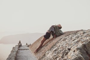 Woman stretching body on stones in