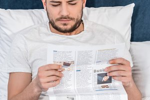 handsome man in pajamas reading news