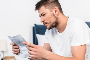handsome serious man reading newspap
