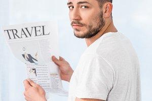 handsome man holding travel newspape